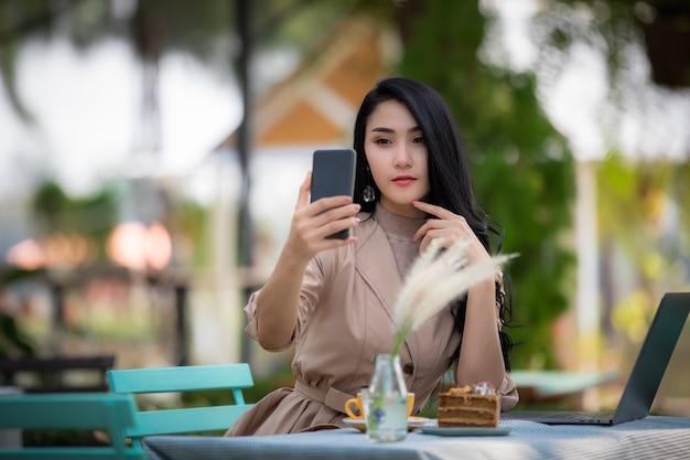 Donne asiatiche di affari che utilizzano selfie sullo smartphone e dolce e caffè del computer portatile sulla tavola nel giardino