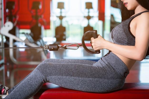 Donne asiatiche di forma fisica che eseguono facendo esercizi che si preparano con il vogatore nella palestra di sport i