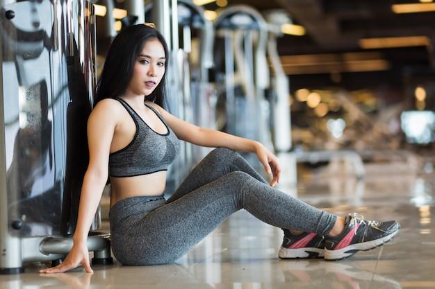 Donne asiatiche di forma fisica che si siedono nel club di salute dell'interno e di forma fisica della palestra di sport