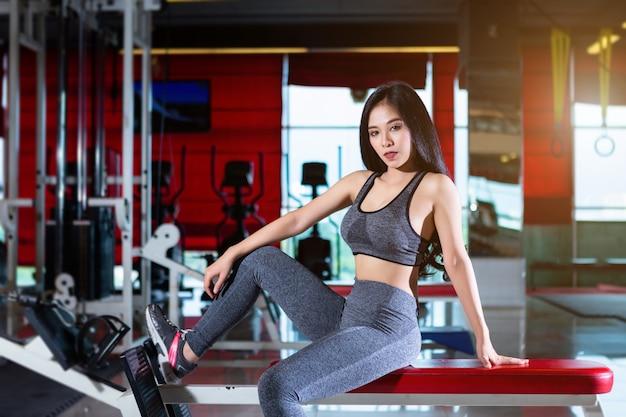 Donne asiatiche di forma fisica che si siedono su un banco nel club di salute dell'interno e di forma fisica della palestra di sport