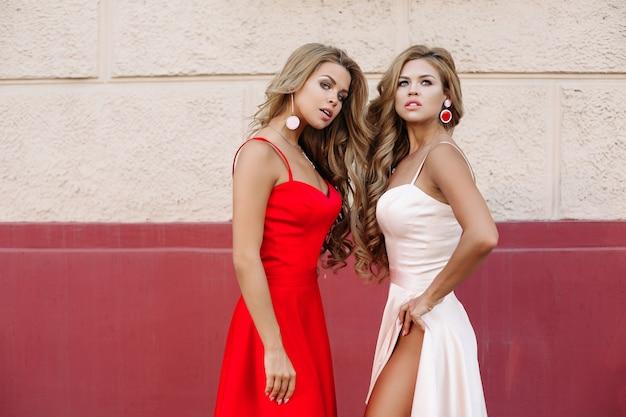 Donne attraenti in abiti eleganti in posa
