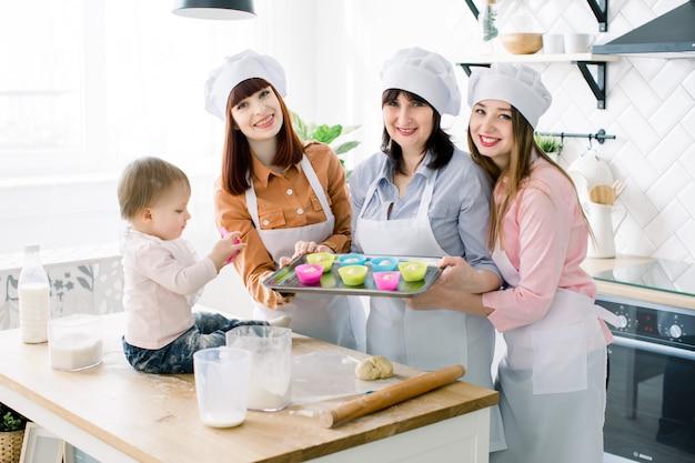Donne attraenti in grembiuli bianchi che cuociono insieme, tenendo la teglia in metallo con forme colorate in silicone per cupcakes e muffin e guardando la fotocamera. la bambina è seduta sul tavolo