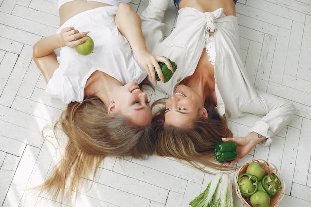 Donne belle e sportive in una cucina con verdure