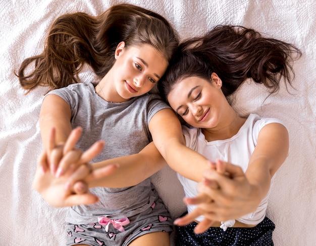 Donne carine con le mani in alto sul letto