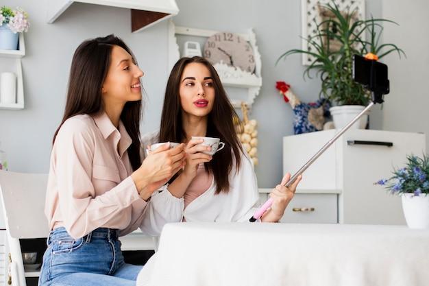 Donne che bevono caffè e prendono selfie