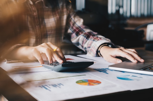 Donne che esaminano i dati in grafici e grafici finanziari con calcolatrice e computer portatile