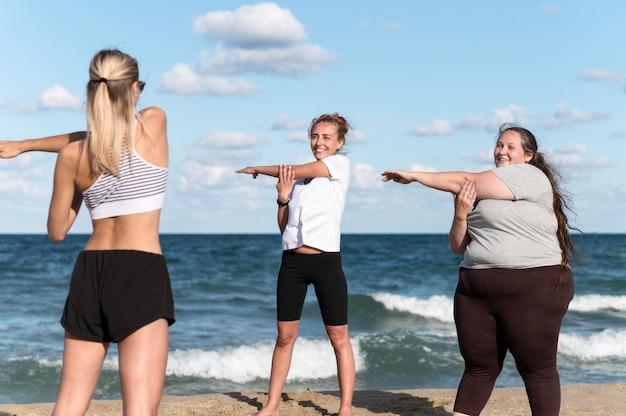 Donne che fanno esercizi in spiaggia
