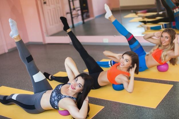 Donne che fanno esercizi per i muscoli della stampa con piccoli fitball