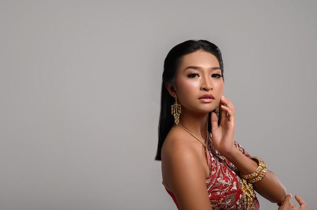 Donne che indossano abiti e mani thailandesi toccando i loro volti