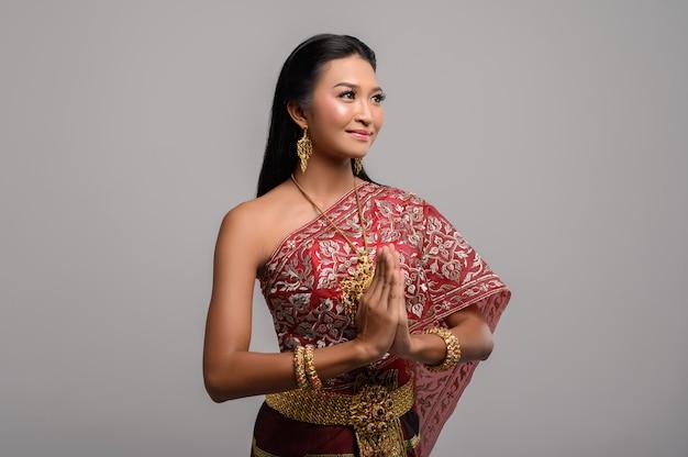 Donne che indossano abiti tailandesi che rispettano, simbolo sawasdee