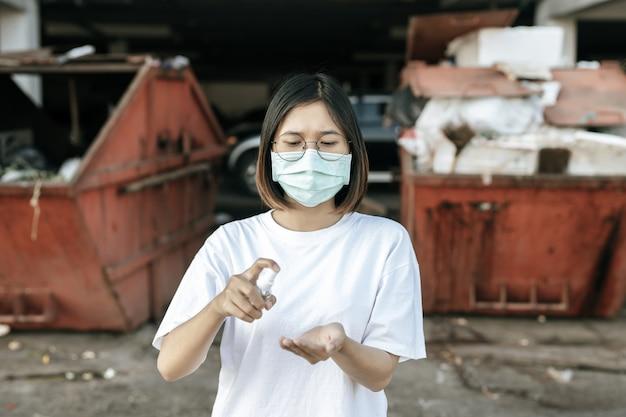 Donne che indossano camicie bianche che premono il gel per lavarsi le mani e pulirle.