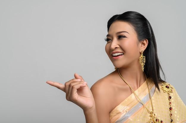 Donne che indossano costumi tailandesi che sono simbolici, puntando le dita