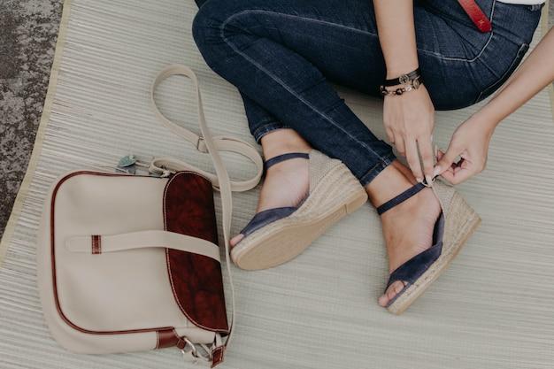 Donne che indossano sandali o scarpe con un portafoglio, una borsa e una borsa