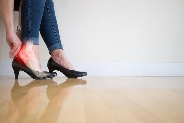 Donne che indossano tacchi alti infiammazione alla caviglia della gamba umana di osso