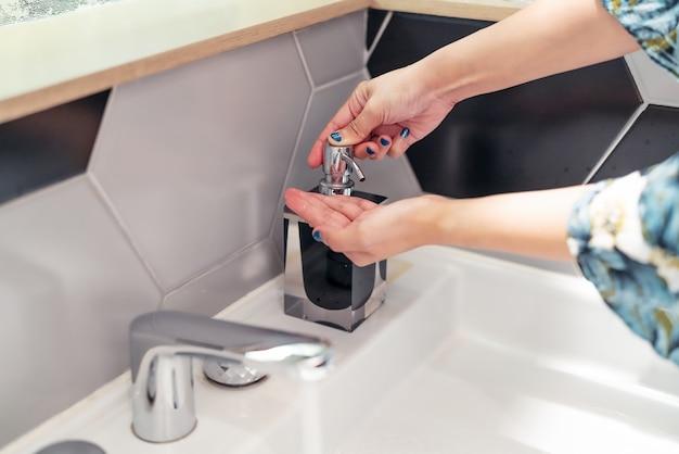 Donne che lavano la mano con sapone liquido in bagno