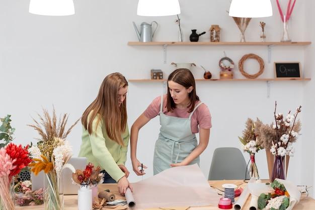 Donne che lavorano nel loro piccolo negozio di fiori