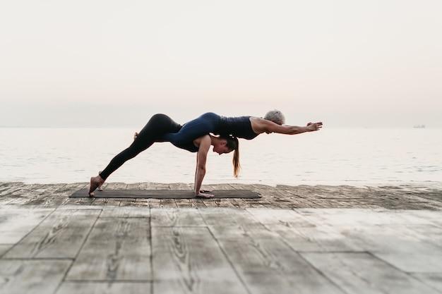 Donne che praticano asana di yoga di acro vicino al mare su alba