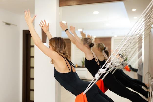 Donne che praticano yoga sulle corde che si estende in palestra. stile di vita in forma e benessere
