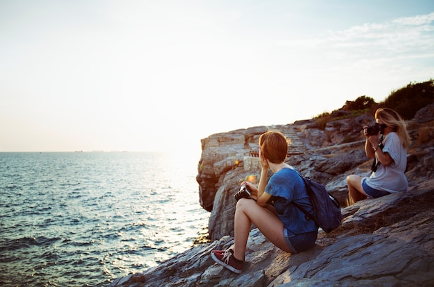 Donne che prendono foto in riva al mare