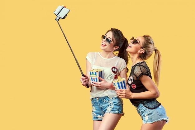 Donne che prendono selfie con popcorn