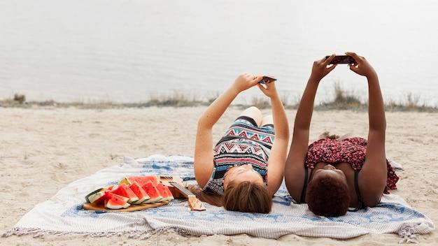 Donne che prendono selfie sulla spiaggia