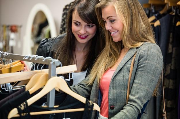Donne che selezionano un vestito mentre fanno shopping per i vestiti