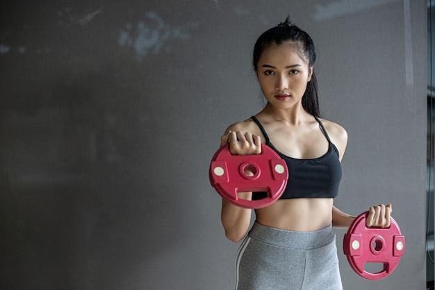 Donne che si esercitano con due piastre di pesi con manubri