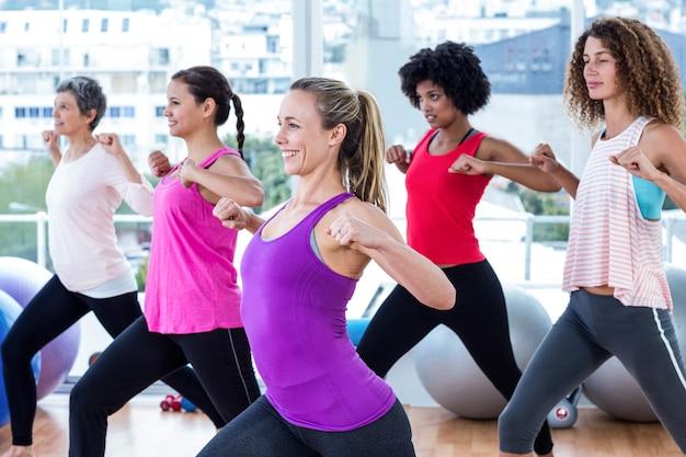 Donne che si esercitano con le mani giunte e stretching