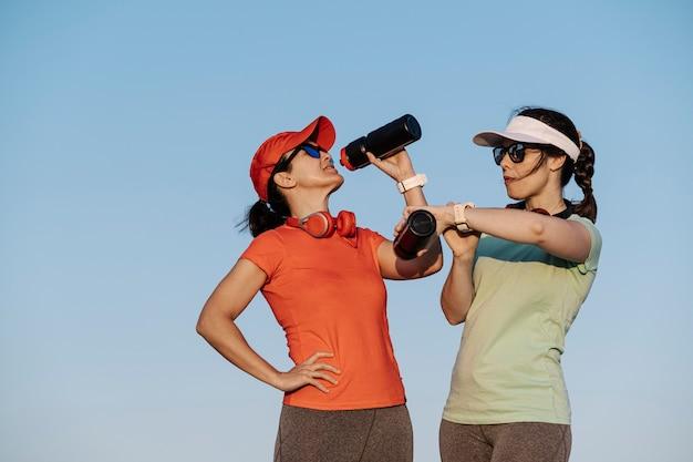 Donne che si idratano con l'acqua e guardano l'orologio dopo la corsa