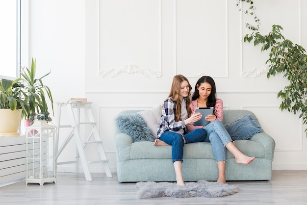 Donne che si siedono insieme sul divano e guardare qualcosa nel tablet