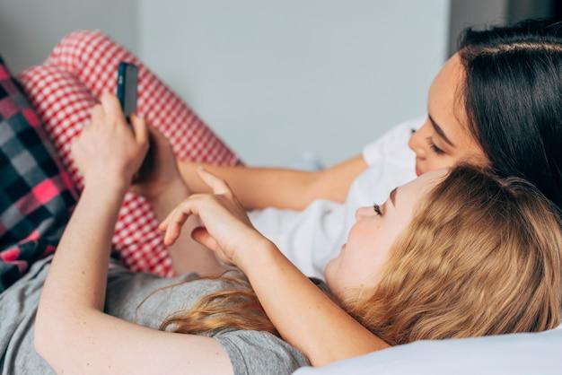 Donne che si stringono a letto e si divertono nel telefono