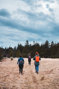 Donne che stanno sul campo marrone circondato dagli alberi verdi sotto le nuvole e il cielo blu bianchi