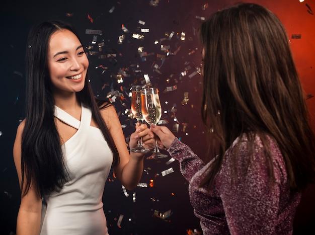 Donne che tostano alla festa per la vigilia di capodanno