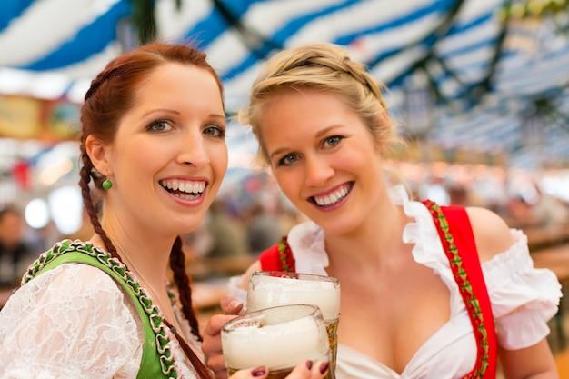 Donne con abiti tradizionali bavaresi o dirndl nella tenda della birra