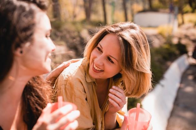 Donne con bevande che ridono e chiacchierano