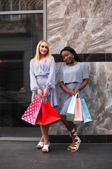 Donne con borse della spesa guardando la fotocamera