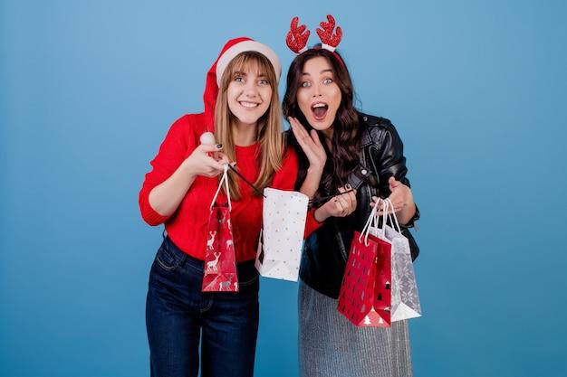 Donne con i regali in sacchetti della spesa variopinti che indossano il cappello di natale e vestiti di inverno isolati sopra il blu