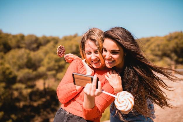 Donne con lecca-lecca prendendo selfie