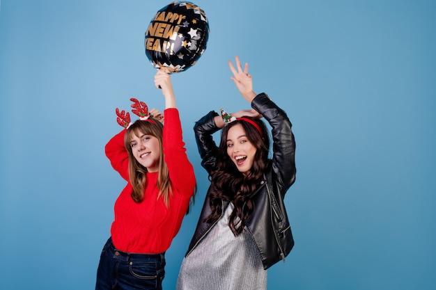 Donne con palloncino felice anno nuovo indossando abiti invernali
