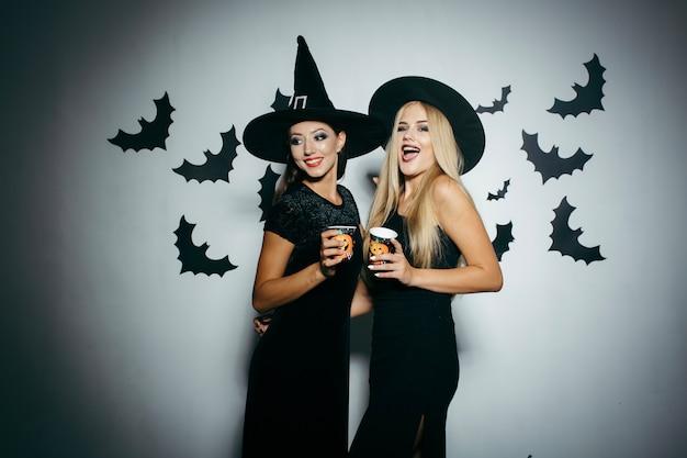 Donne con tazze sul partito di halloween