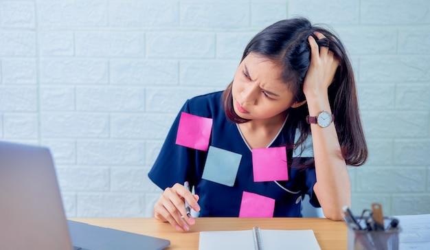 Donne d'affari asiatiche che soffrono di mal di testa a causa del duro lavoro e dall'uso del computer per molto tempo, post note sul corpo nella stanza della scrivania.
