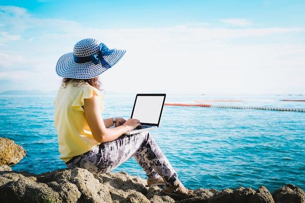 Donne d'affari che lavorano con il computer portatile. lavoro e viaggi in mare in estate.