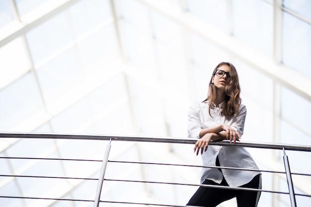 Donne d'affari di successo in piedi guardando attraverso il balcone nel centro ufficio moderno vestite in maglietta bianca