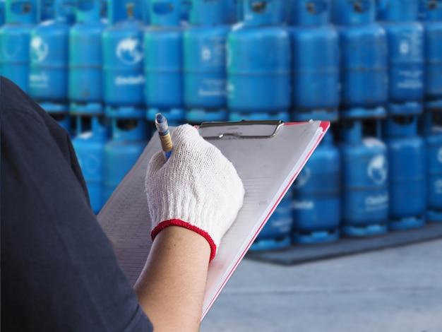 Donne dei lavoratori di mani che lavorano nel magazzino del gas di distribuzione