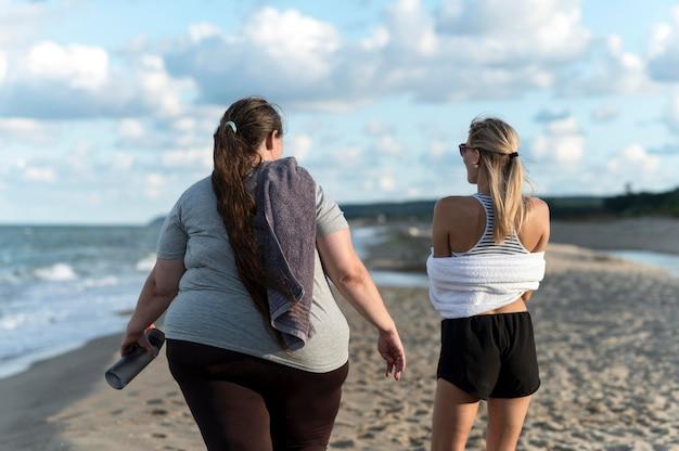 Donne del colpo medio in spiaggia