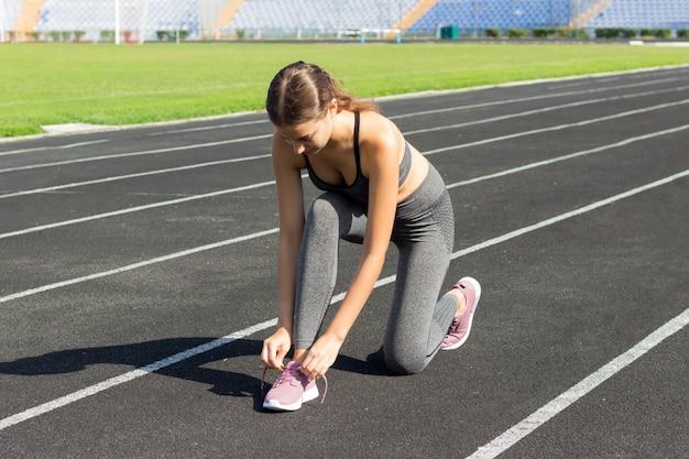 Donne del corridore che legano i lacci delle scarpe che si preparano per la corsa sulla pista di corsa nello sport dello stadio e nel concetto di forma fisica