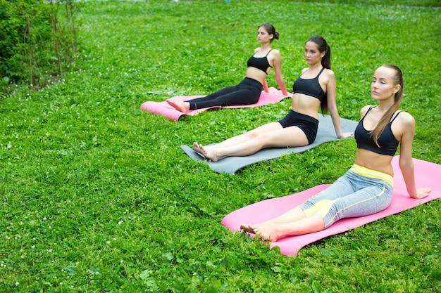 Donne del gruppo che praticano yoga nel parco. meditazione all'aperto.