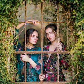Donne del primo piano che guardano attraverso le barre