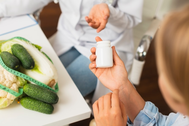 Donne del primo piano con le verdure e il contenitore della pillola