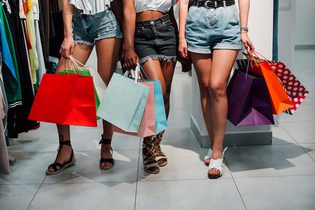 Donne dell'angolo alto che camminano nel negozio di vestiti